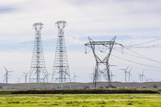 High voltage electricity towers and lines crossing the Sacramento-San Joaquin Delta; Wind turbines visible on the hills in the background; Solano County, California
