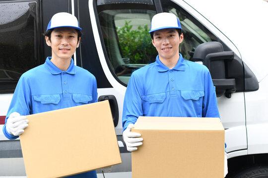 車の前で作業服を着た複数の男性が引っ越しの段ボールを運ぶイメージ