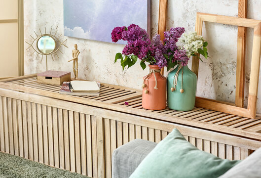 Vases with lilac flowers in interior of stylish room