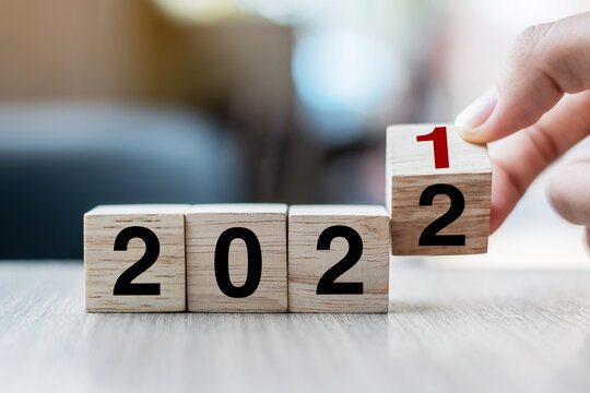 Businessman hand holding wooden cube with flip over block 2021 to 2022 text on table background. Resolution, strategy, solution, goal, business and New Year holiday concepts