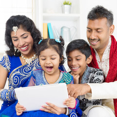 Fototapeta Happy Family Wearing Traditional Clothing While Using Digital Tablet At Home obraz