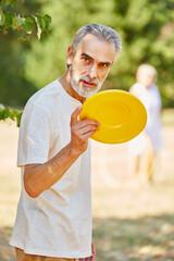Fototapeta Portrait Of Senior Man Holding Plastic Disc obraz