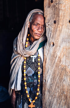 Senior wrinkled woman wearing cultural necklace with cloak leani