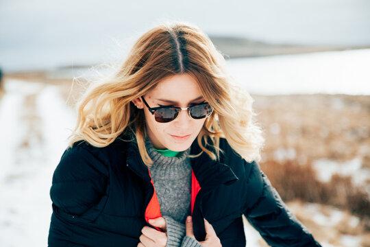 Freezing woman walking on snowy road