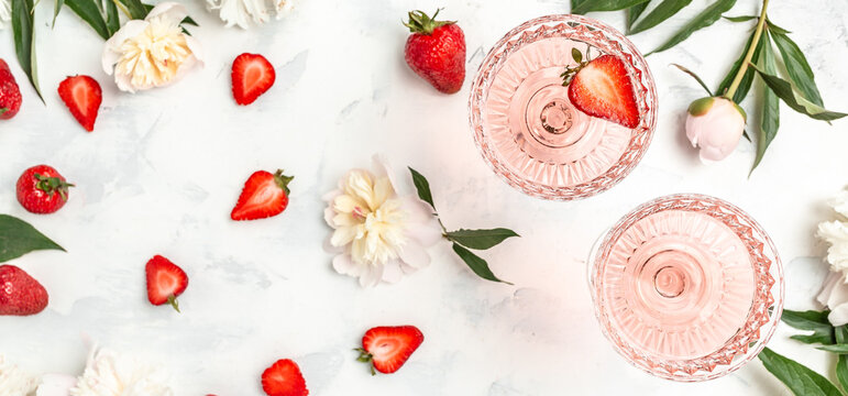 Glass Of White Wine, sweet fresh strawberries and Peony Flowers. Summer drink for party, wine shop or wine tasting concept