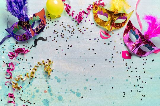 Masquerade masks and party accessories on blue background