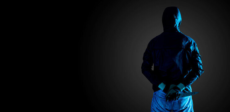 murder, kill and people concept - Criminal or bandit holding a knife behind his back,Isolated on black background