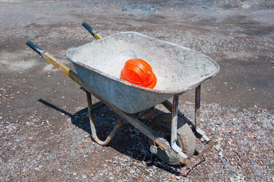 The wheelbarrow is at a construction site, there is a helmet in it.