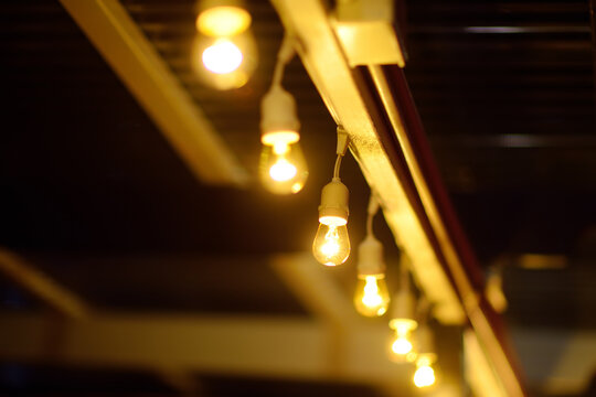 Photo of string lights hanging in restaurant or cafe in the garden at evening time. Fashion decoration with bulbs for night summer party. Outdoor electric lamps