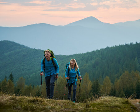 Two persistent professional hikers with trekking poles and backpacks moving on mountain hills against a background of green forest, mountain beskids and purple sky looking ahead.