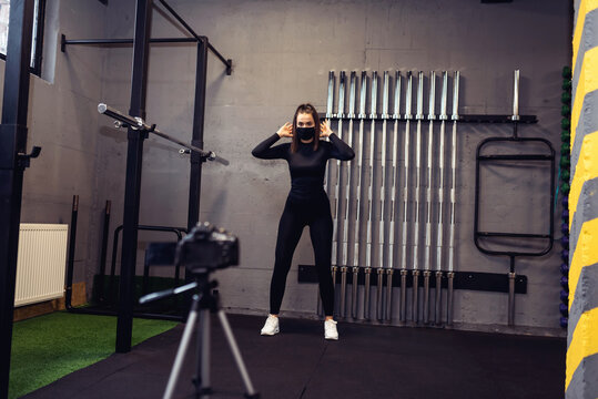 Athletic fitness instructor with a protective mask, gym dumbbell, and balance gym workout exercises live on camera for sportive followers on social media. Home fitness workout class live streaming.