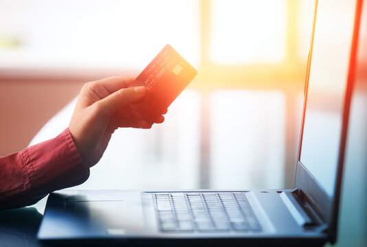 Hand holding credit card in their hands using their laptop device to make purchases online and conduct financial transactions