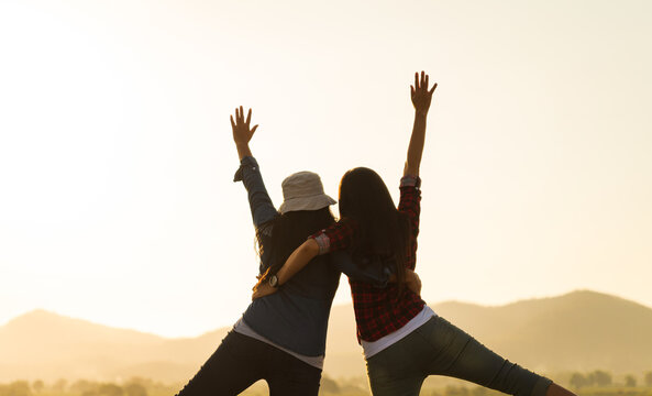 Young women are having fun with raised arms together in front of mountain during sunset. Happiness, success, friendship and community concepts.