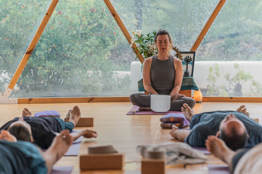 People lying on yoga mats with eyes closed while trainer making sound from bowl in domed hall