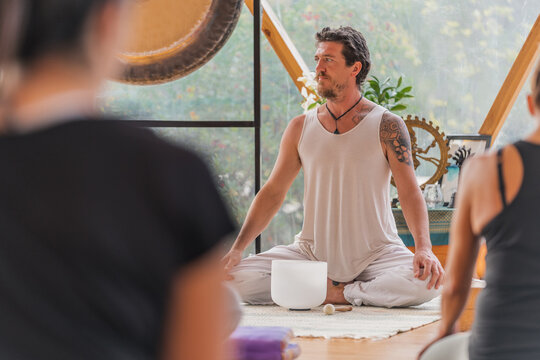 Attentive people sitting on yoga mat before trainers in decorated room