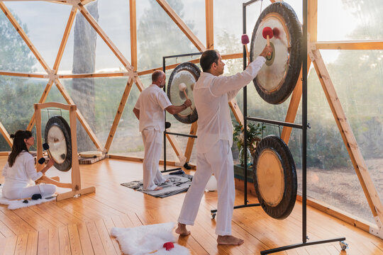 People in white robes hitting gong in bright room