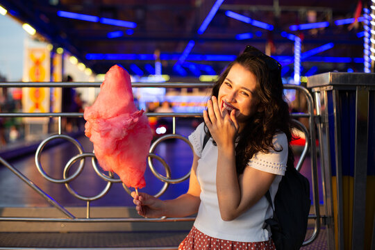 Funny young woman eating cotton candy at fairground