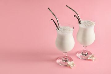 Glasses with tasty vanilla milkshake on color background