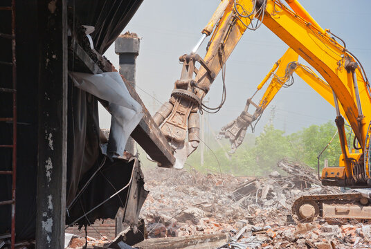 Two demolators destroy the building and remove the debris.
