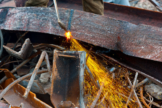 A worker cuts an iron beam with a gas cutter.