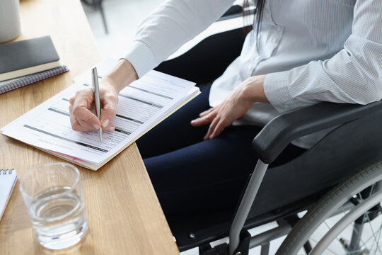 Disabled woman in wheelchair filling out application for employment closeup