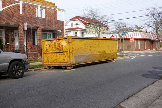 Old long yellow dumpster on an asphalt street in front of a brick building being renovated