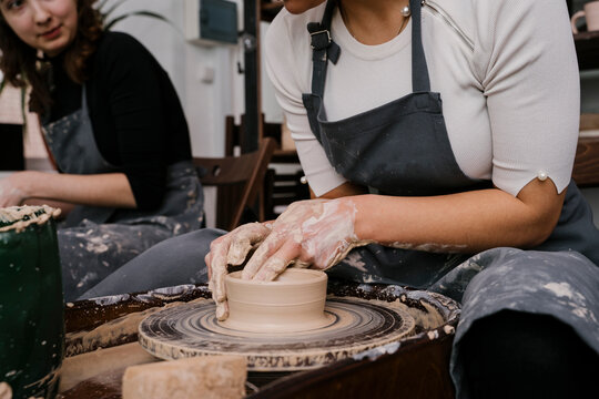 Women molding clay mass behind pottery wheel