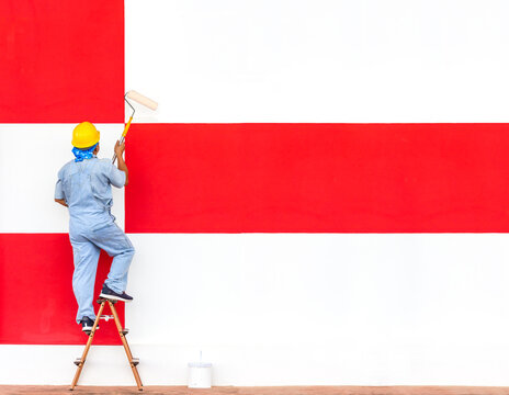 painter man at work painting white and red checkered pattern wall with a roller on ladder
