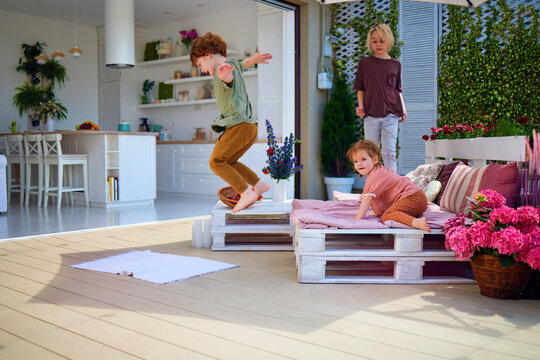 cute kids having fun, playing on the summer patio at home. furnished terrace with open space kitchen