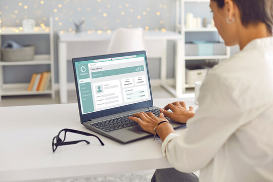 Woman enjoys online banking for work, business or personal needs. Businesswoman or remote worker sitting at desk at home, using laptop computer, managing her bank account and transferring money online