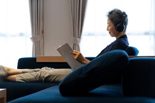 ヘッドホンをつけて読書をする日本人シニア女性