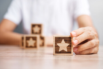 Man hand holding Star block. Customer choose rating for user reviews. Service rating, ranking,...