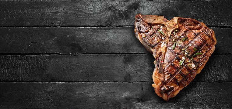 Delicious T bone steak on dark wooden table