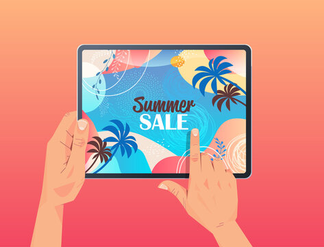 human hands using tablet pc with summer sale banner flyer or greeting card on screen horizontal