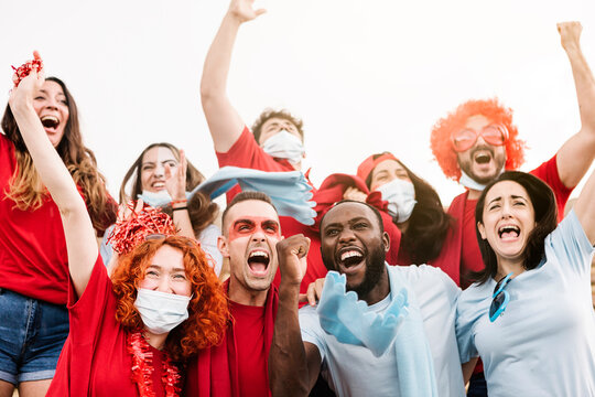 Group of multiracial supporters wearing protective face mask screaming while supporting their team in the stadium - New normal for live sports concept - Focus on black man face