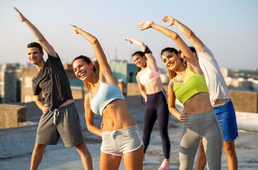 Obraz Group of happy friends working out together outdoors. Fitness, training, sport and people concept - fototapety do salonu