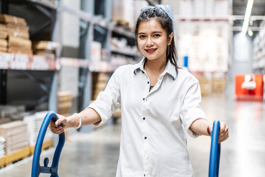 Asian young woman walks with shopping cart walking for choosing new furniture in big store warehouse.