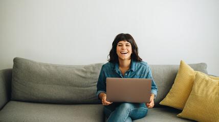 Happy businesswoman with laptop sitting in lobby - fototapety na wymiar