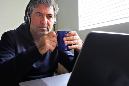 Worried unemployed mature adult man watching bad news on a laptop.