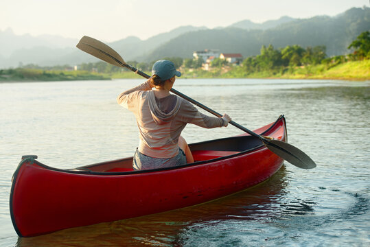 Woman rowing oars while floating on kayak on river against background of houses in countryside.