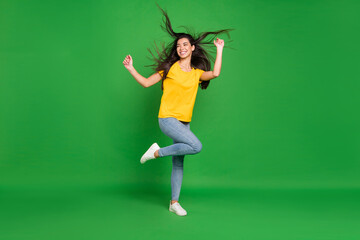 Full length body size photo girl with long brunette hair dancing at party looking copyspace isolated vivid green color background