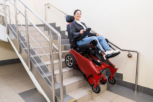 Caucasian woman in electric caterpillar wheelchair climbs up stairs.