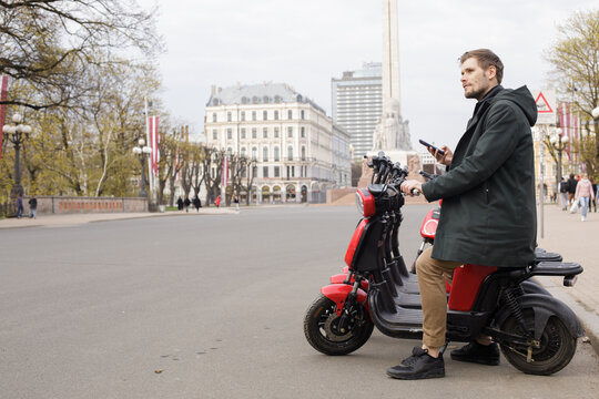 Transportation ecology. Green sustainable mobility Young man unlocks an e-scooter with his mobile phone. Electric scooter new way city. Green transportation. Sustainable climate neutral cities goals.