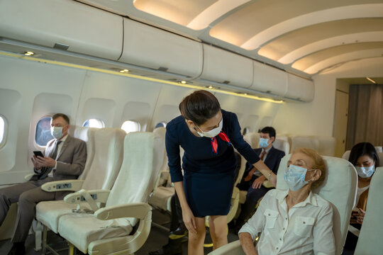 Air hostess wearing protective mask to Protect Against Covid-19 take care and check the orderliness of the plane passengers before departure,New normal travel after covid-19 pandemic concept .