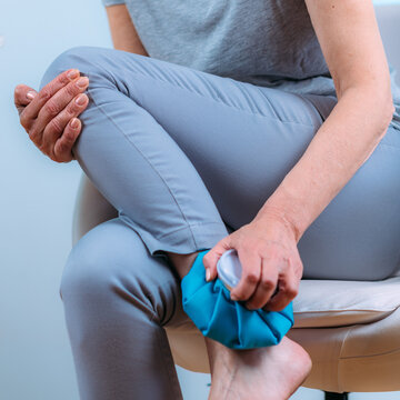 Ankle Pain Treatment. Senior Woman Holding Ice Bag Compress on a Painful Ankle Joint.