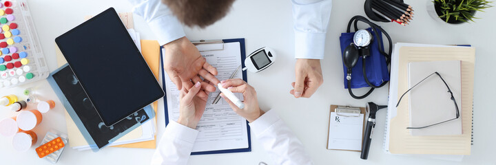 Doctor taking blood test from patients finger with lancet top view - fototapety na wymiar