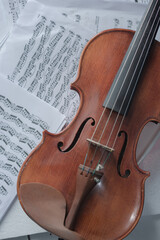Close up detail on violin body, bow and music notes background. Classic instrument with copy space...