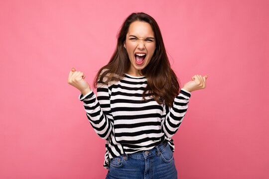 Portrait of young positive happy beautiful brunette woman with sincere emotions wearing casual striped pullover isolated on pink background with empty space and celebrating victory saying yeah