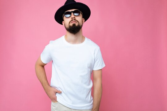 Horizontal photo shot of handsome brunette unshaven young man with beard wearing casual white t-shirt for mockup black hat and stylish sunglasses isolated over pink background wall looking at camera
