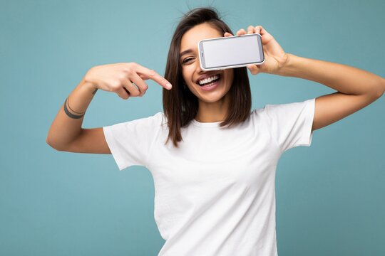 Photo of beautiful smiling young woman good looking wearing casual stylish outfit standing isolated on background with copy space holding smartphone showing phone in hand with empty screen display for